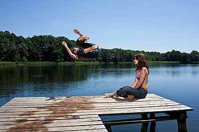 Guy jumps into lake with arms outstretched as girl watches on jetty - p30119614f by Carl Smith