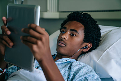 Black boy laying in hospital bed listening to digital tablet - p555m1532461 by FS Productions