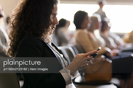 Businesswoman using smart phone in conference audience - p1192m2123182 by Hero Images