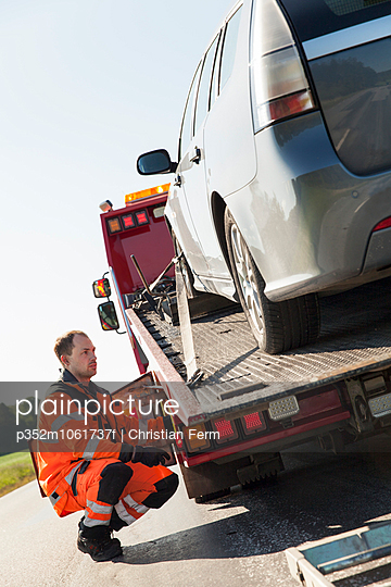 Sweden, Sodermanland, Salem, Man looking at car on tow truck