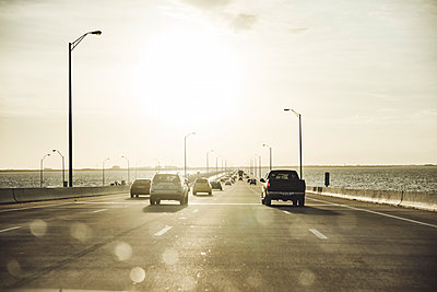 Cars moving on highway over sea against sky at sunset, Miami, USA - p300m2143587 by Christophe Papke