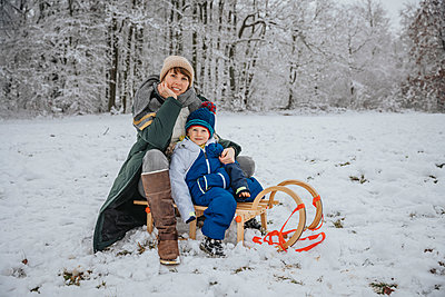 Mother and son sitting on sled at snowy field during winter - p300m2267737 by Mareen Fischinger