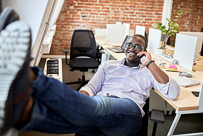 Smiling businessman with feet up talking on smart phone at office - p300m2283010 by Zeljko Dangubic