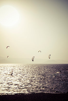 Greece, Cyclades, Naxos, Mikri Vigla, Orkos Beach, Kite- and windsurfer at sunset - p300m948950 by Kristian Peetz