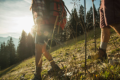 Austria, Tyrol, Tannheimer Tal, young couple hiking in sunlight on alpine meadow - p300m978827f by Uwe Umstätter