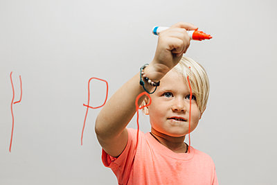 Boy writing reversed letter P onto glass wall - p429m1504963 by JFCreatives
