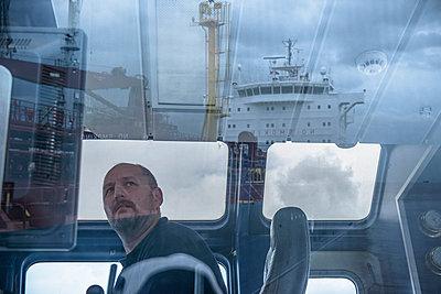 Worker in tugboat wheelhouse at window - p429m747090f by Monty Rakusen
