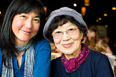 Older Japanese mother and daughter smiling in restaurant - p555m1302170 by Jed Share/Kaoru Share