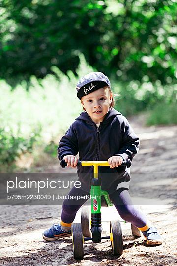 Kleinkind mit Dreirad im Park - p795m2230049 von JanJasperKlein