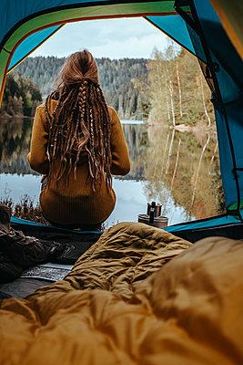 Frau mit Kaffee sitzt vor ruhigem Bergsee - p1455m2203731 von Ingmar Wein
