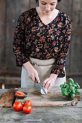 Woman preparing Caprese Salad - p300m2012394 von Alberto Bogo