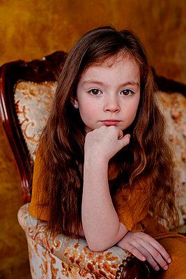 Portrait of little girl sitting on lounge chair - p300m2121791 von Oxana Guryanova