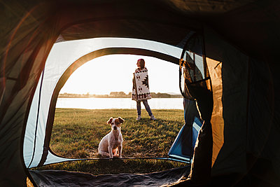 Woman wrapped in shawl camping with dog against lake seen through tent - p300m2242425 by Eva Blanco