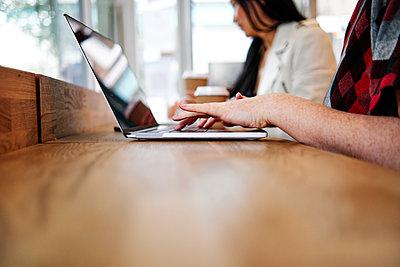 Woman using laptop by female friend in coffee shop - p300m2287289 by Angel Santana Garcia