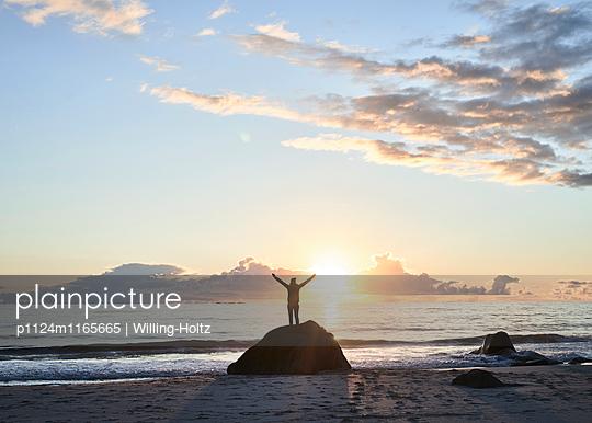Frau steht auf Stein am Strand im Sonnenuntergang - p1124m1165665 von Willing-Holtz