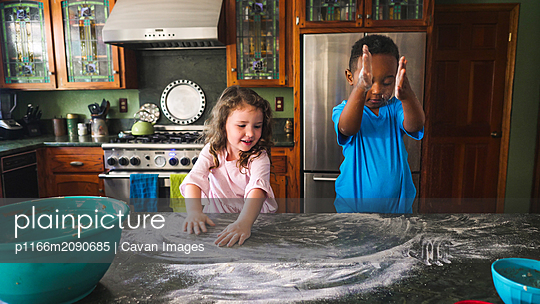 Boy and girl playing with flour in the kitchen - p1166m2090685 by Cavan Images