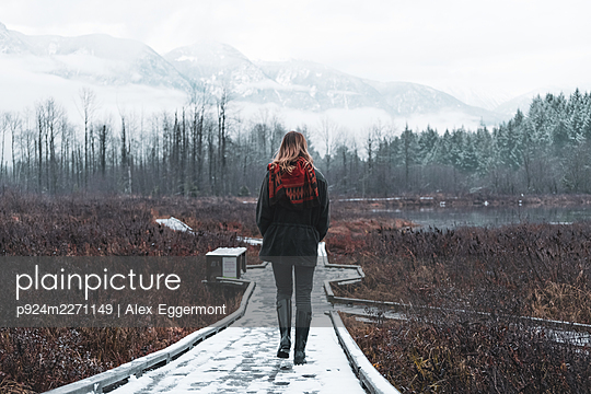 Rear view of woman on walkway Lillooet Lake, British Columbia, Canada - p924m2271149 by Alex Eggermont