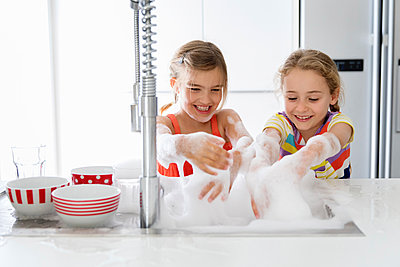 Happy sisters playing with soap sud while washing dishes in kitchen sink at home - p1166m2112721 by Cavan Images