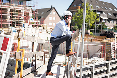 Man wearing hard hat on cell phone on construction site - p300m2005458 by Robijn Page