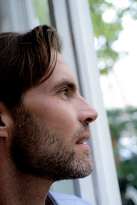 Close-up of man looking out of window - p300m2042000 by harrylidy