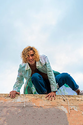 Young smiling blond man on a wall, looking at camera - p300m2160053 by VITTA GALLERY