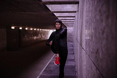 Female athlete warming up before running in pedestrian underpass - p300m2188250 by Studio 27