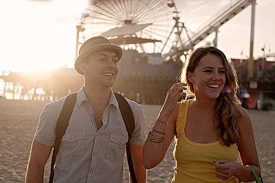 Young man and woman (23-28) walking on beach near Santa Monica pier, Los Angeles, California, USA - p300m2281412 von LOUIS CHRISTIAN