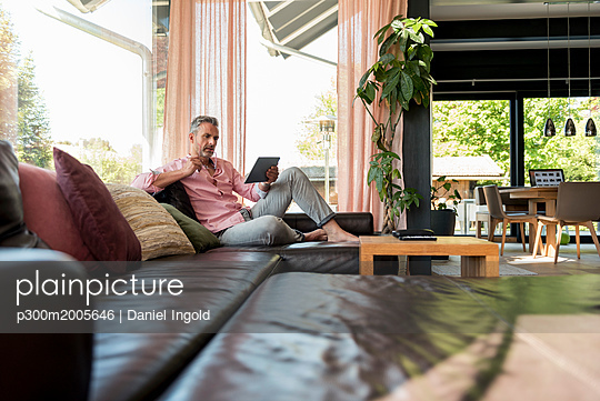 Mature man sitting on couch at home using a tablet - p300m2005646 von Daniel Ingold