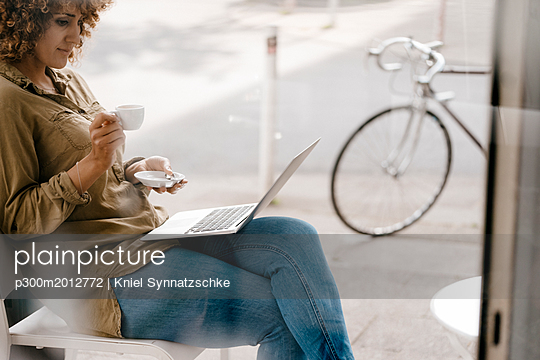 Woman working in a cafe, drinking coffee, using laptop - p300m2012772 von Kniel Synnatzschke