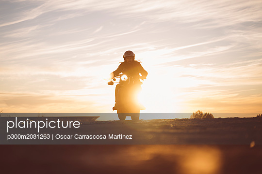 Silhouette of man riding custum motorcycle at sunset - p300m2081263 by Oscar Carrascosa Martinez