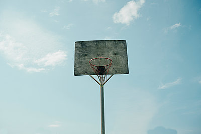 Old basketball backboard under blue sky - p1166m2157292 by Cavan Images