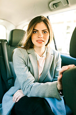 Portrait of young businesswoman sitting on backseat of a car - p300m1587117 von Valentina Barreto