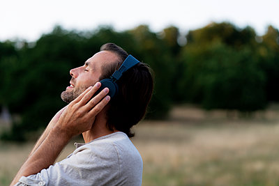 Smiling man listening to music with headphones in the nature - p300m2042041 von harrylidy