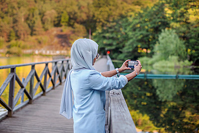 Woman on bridge taking photo - p312m2217196 by Pernille Tofte