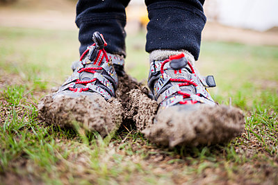 Close up of boy shoes in mud - p343m1446659 by Steve Glass