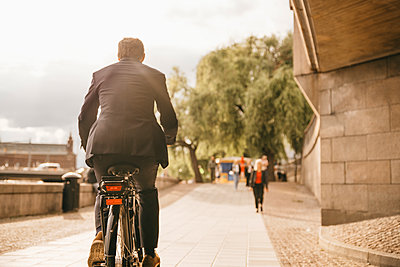 Rear view of businessman riding bicycle on footpath in city - p426m2145632 by Maskot