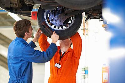College mechanic students inspecting car wheel in repair garage - p429m1227381 by Peter Muller