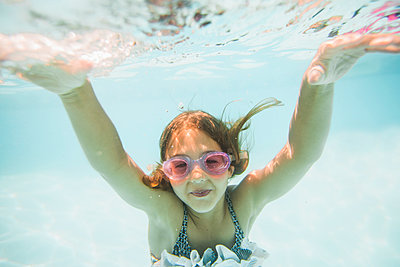 Caucasian girl swimming underwater in swimming pool - p555m1411533 by John Fedele