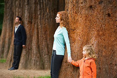Mother and daughter leaning against tree, father standing separate in background - p624m1487346 by Eric Audras