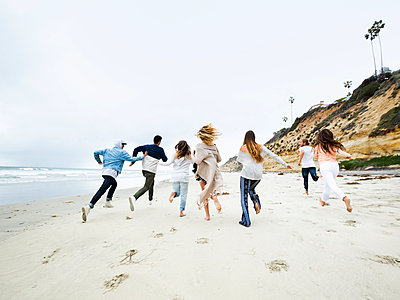A group of young men and women running on a beach, having fun. - p1100m1038930 by Mint Images
