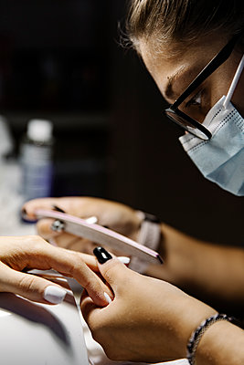 Woman in mask shaping nails of client while working during epidemic - p1166m2216689 by Cavan Images