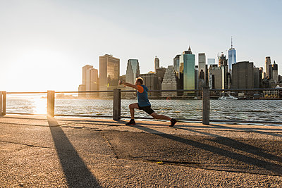USA, Brooklyn, man doing stretching exercises in front of Manhattan skyline in the evening - p300m1205767 by Uwe Umstätter