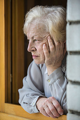 A senior woman leaning on a window sill; looking contemplative - p301m844153f by Vladimir Godnik