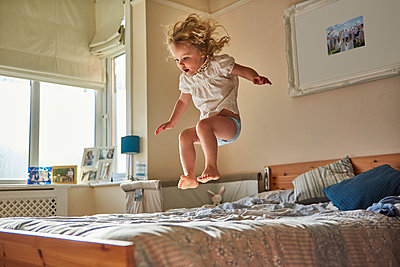 Female toddler jumping mid air on bed - p429m1569287 by J J D