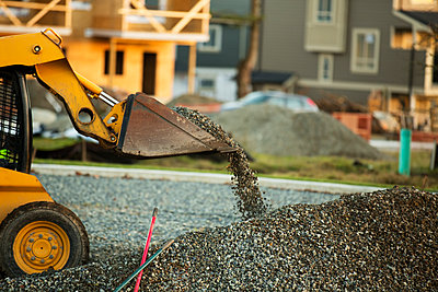 Small front end loader moving and placing gravel in a park area for new home construction; Langley, British Columbia, Canada - p442m1580562 by LJM Photo