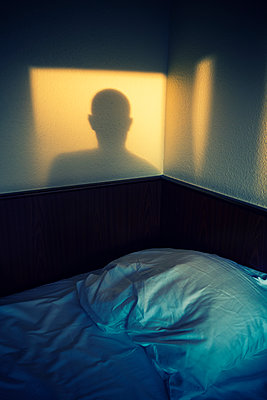 Shadow of a man on the bedroom wall  - p794m1146124 by Mohamad Itani