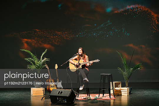 Female musician playing guitar on stage - p1192m2123176 by Hero Images