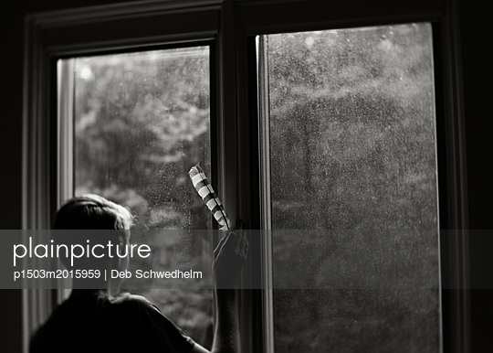 Boy with Feather Looking Out Window - p1503m2015959 by Deb Schwedhelm