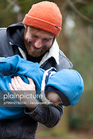 Father holding his baby boy in his arms - p795m2192232 by JanJasperKlein