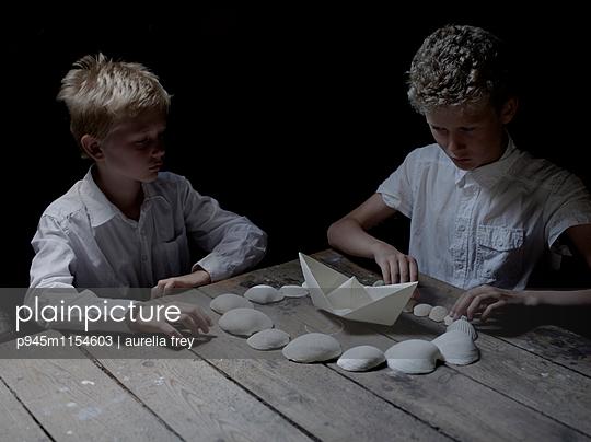 Zwei Jungen spielen mit Muscheln und einem Papierboot - p945m1154603 von Aurelia Frey